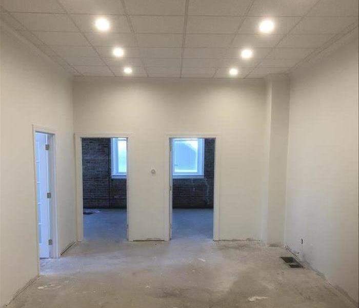Room with three doorways and white walls with drop ceiling with 6 lights