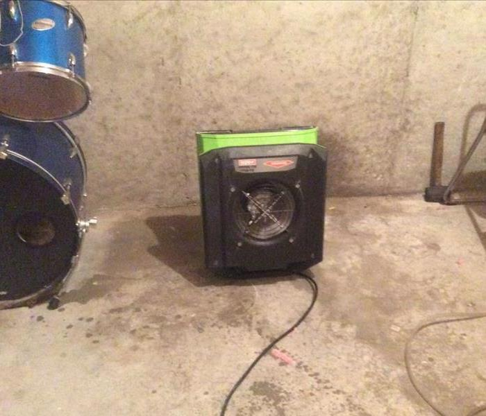 Basement with concrete wall and floor with an air mover placed to dry out water damage.  Blue drum set in view.