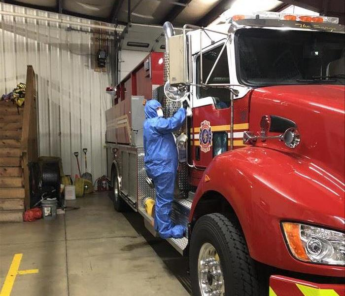 SERVPRO employee wearing a blue PPE suit and rag cleaning an EMS vehicle for a proactive cleaning
