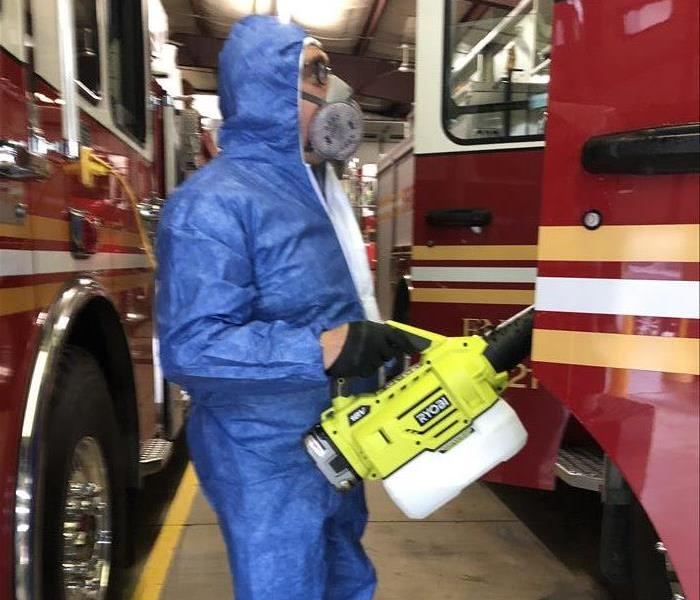 SERVPRO employee wearing a blue PPE suit fogging a firetruck to for a proactive virus cleaning